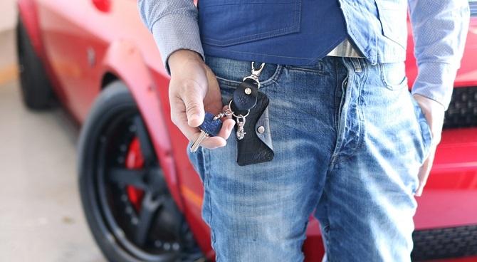 赤い車の前でsスマートキーを操作する男性