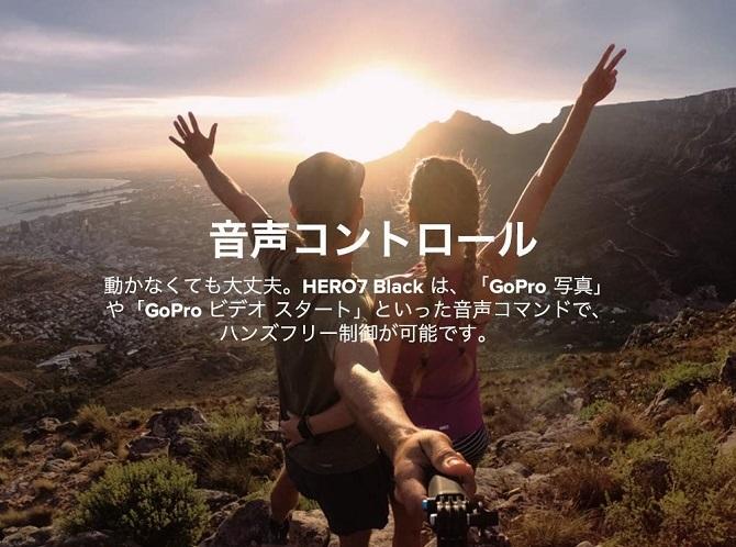 山の上で手を挙げる人